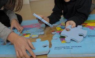 Des enfants jouent avec un tapis-puzzle, le 12 décembre 2010.