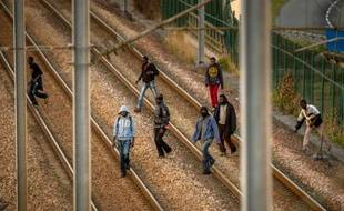 Des migrants sur les rails du site d'Eurotunnel à Coquelles, le 12 août 2015