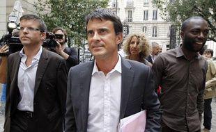 Manuel Valls, avec son directeur de campagne, Luc Carvounas (à gauche) et son porte-parole, Ali Soumaré (à droite), arrivent au siège du PS à Paris, le 22 août 2011.