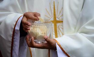 Image d'illustration d'un prêtre donnant la communion.