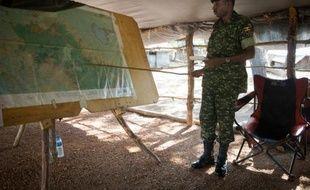 Un soldat de l'UPDF, l'armée ougandaise engagée dans la lutte contre la guerilla de la LRA, montre une carte à la base militaire de Kocho en Centrafrique, le 24 juin 2014