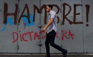 Un homme marche devant les mots faim et dictature écrits sur un mur de Caracas.