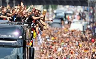 """Les joueurs allemands montrent la Coupe du monde aux supporteurs, du haut d'un """"camion à impériale"""", dans les rues de Berlin le 15 juillet 2014"""