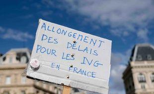 Une manifestante tient une pancarte réclamant l'