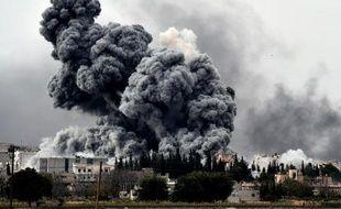 Une épaisse fumée noire s'élève de la ville de Kobané où les forces kurdes résistent farouchement aux jihadistes de l'EI, le 12 octobre 2014 à Mursitpinar, à la frontière syro-turque
