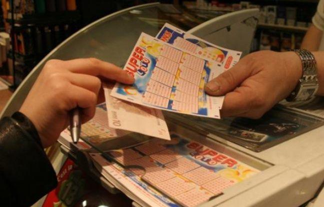 Un client achète une grille de Super Loto chez un buralistes parisien le vendredi 13 août 2010.