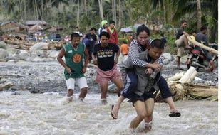 Des Philippins traversent une rivière à New bataan, le 5 décembre 2012, après le passage du typhon Bopha