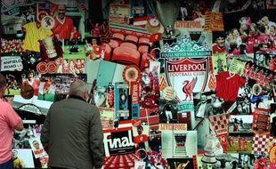 Un homme observe le collage de photographies qui orne la boutique du Liverpool FC