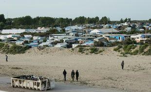 Des migrants marchent près de la  «jungle» de Calais, le 26 juillet 2016