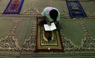 Illustration. Un homme lit le Coran sur un tapis de prière dans une mosquée.