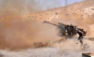 Un soldat syrien ouvre le feu le 17 mai 2015 avec une pièce d'artillerie sur des positions des islamistes du groupe EI au nord-est de Palmyre