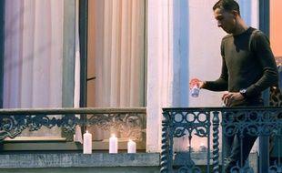 Mohamed Abdeslam, le frère d'un des kamikazes qui s'est fait sauter à Paris, dispose discrètement des bougies au balcon de la maison familiale, le 18 novembre 2015 à Molenbeeck