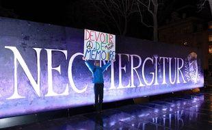 Un Parisien pose devant la devise de Paris pour les 1 an de commémorations aux attentats de janvier 2015.