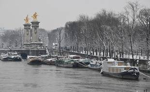 Des péniches sous la neige près du pont Alexandre III à Paris