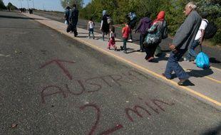 """Des migrants passent près d'un message """"Autriche-2 minutes"""", écrit au sol à la frontière austro-hongroise, près de Nickelsdorf, du côté autrichien, le 12 septembre 2015"""