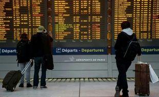 Des passagers devant le tableau des départs le 26 janvier 2016 à l'aéroport Charles-de-Gaulle à Roissy