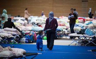 Des migrants dorment dans la hall d'un parc olympique à Berlin le 12 septembre 2015.