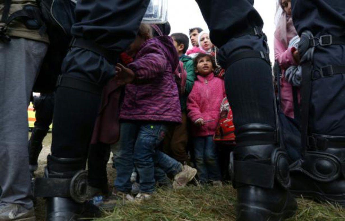 Des enfants parmi les migrants sont encadrés par des policiers slovènes, le 22 octobre 2015 près du village de Rigonce en Slovénie – STRINGER AFP