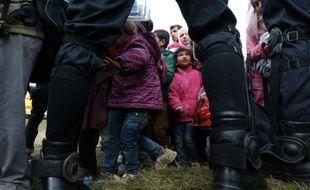 Des enfants parmi les migrants sont encadrés par des policiers slovènes, le 22 octobre 2015 près du village de Rigonce en Slovénie