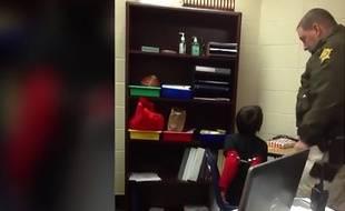 Capture d'écran de l avidéo diffusée par l'ACLU, montrant Kevin Sumner, le shérif adjoint du comté de Kenton, dans le Kentucky, s'adresser à un petit garçon, menotté, les bras derrière le dos, et assis sur une chaise d'une classe de l'école primaire Latonia, à Covington, près de Cincinnati.