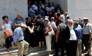 Des retraités font la queue le 29 juin 2015 dans le centre d'Athènes, à l'extérieur d'une agence de la Banque nationale de Grèce pour savoir quand et comment ils pourront toucher leur pension
