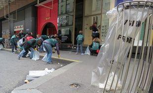 Les membres du collectif Greenbird nettoient bénévolement les abords des Galeries Lafayettes, dimanche 21 février 2016, à Paris.