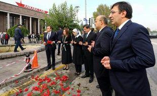 Photo fournie le 13 octobre 2015 par le service de presse du ministère turc des Affaires étrangères montrant le Premier ministre Ahmet Davutoglu et d'autres membres du gouvernement priant sur le site de l'attentat d'Ankara