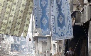 Un milicien du régime marche sous des tapis servant à contrer les snipers dans une rue dévastée de la banlieue de Damas, en Syrie.