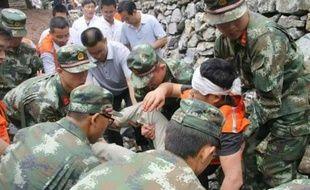 Des secouristes portent une victime du glissement de terrain dans la province du Shaanxi, photo prise le 12 août par un téléphone mobile