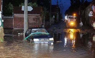 Des habitants de Villers-Plouich utilisent un tracteur pour traverser une des rues inondées du village, le 11 septembre 2008, dans l'agglomération cambraisienne.