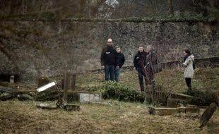 Des enquêteurs examinent le 16 février 2015 les tombes profanées du cimetière juif de Sarre-Union, dans le Bas-Rhin