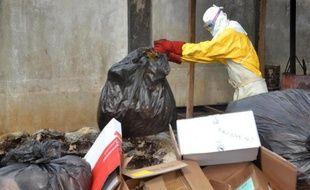 Un travailleur médical traite des déchets des malades du virus Ebola, le 8 décembre 2014 à Conakry, en Guinée, l'un des pays les plus touchés par l'épidémie