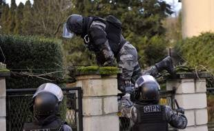 TOPSHOTS Members of the French police special force GIPN carry out searches in Corcy, northern France, on January 8, 2015 as part of an investigation into a deadly attack the day before by armed gunmen on the Paris offices of French satirical weekly Charlie Hebdo. A huge manhunt for two brothers suspected of massacring 12 people in an Islamist attack at a satirical French weekly zeroed in on a northern town on January 8 after the discovery of one of the getaway cars. As thousands of police tightened their net, the country marked a rare national day of mourning for January 7's bloodbath at Charlie Hebdo magazine in Paris, the worst terrorist attack in France for half a century. AFP PHOTO / FRANCOIS LO PRESTI