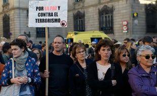 """Un homme brandit une pancarte """"Pour la paix et contre le terrorisme"""" durant une minute de silence en hommage aux victimes de l'attaque de Paris, le 14 novembre 2015 à Barcelone"""