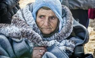 Une femme âgée arrive en chaise roulante dans le village serbe de Miratovac en provenance de Macédoine, le 28 janvier 2016