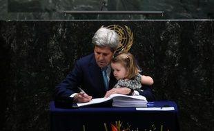 Le secrétaire d'Etat américain John Kerry signe l'accord sur le climat tenant sa petite-fille, à l'ONU à New York, le 22 avril 2016