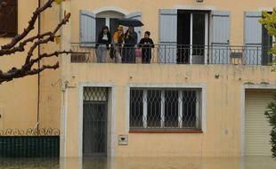 Des gens sur un balcon après les inondations dans le village du Muy, le 24 novembre 2019 Valery HACHE / AFP