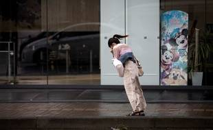 Une japonaise affronte les vents violents après le passage d'un typhon en 2018.