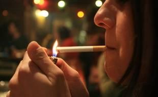 Une femme allumant une cigarette.