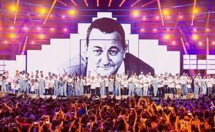 Artistes et bénévoles des Enfoirés sur la scène de l'Arkéa Arena devant le portrait de Coluche.