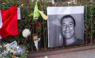 Un portrait d'Ahmed Merabet devant le siège de Charlie Hebdo le 11 janvier 2015 à Paris