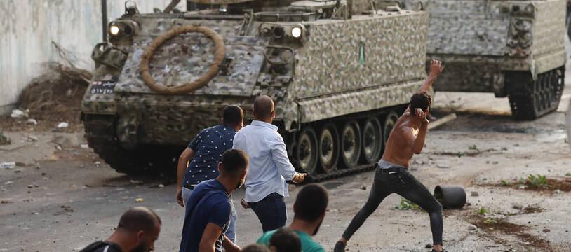 Les partisans du Premier ministre désigné Saad Hariri qui a démissionné jeudi s'affrontent avec des soldats libanais à Beyrouth, Liban, le jeudi 15 juillet 2021.