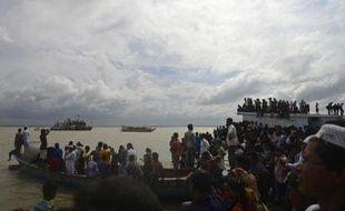 Des passants aux côtés des rescapés du naufrage d'un ferry sur le fleuve Padma, au sud de Dacca, le 4 août 2014