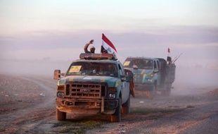Des membres chiites des forces gouvernementales brandissent le drapeau irakien à Ad-Dawr le 6 mars 2015 lors d'une opération destinée à reprendre Tikrit tombée sous le joug de l'Etat islamique