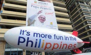 Un poster géant et un ballon gonflable célébrent la venue du pape François aux Philippines, le 10 janvier 2015 dans une rue de Manille
