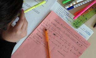 Un lycéen de terminale vu de haut planchant sur sa copie de philosophie du baccalauréat le &7 juin 2013