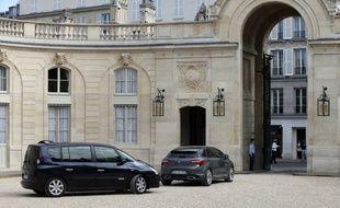La voiture présidentielle et son escorte dans la cour de l'Elysée.