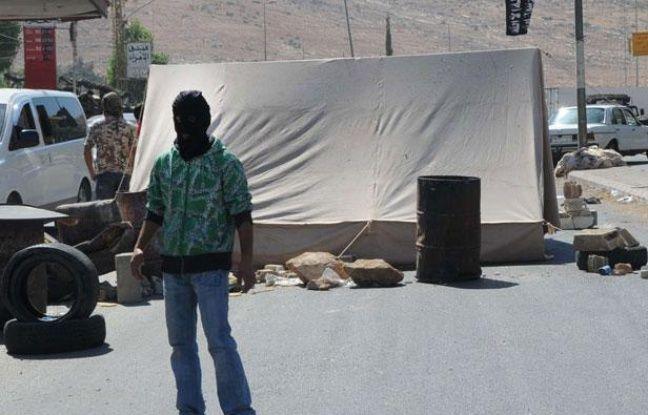 Un homme masqué appartenant à un groupe sunnite, bloque une route à la frontière libano-syrienne, à Masnaa, dans l'Est du Liban, le jeudi 16 août 2012