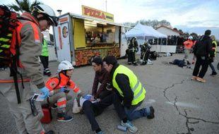 """Des services de secours prennent en charge un patient, lors de la simulation d'attaque terroriste dans une """"fans zone"""", le 17 mars 2016"""