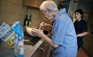 Une personne âgée prépare un gâteau sous l'oeil attentif d'une aide de vie, en Bourgogne en juillet 2011